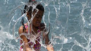 In this file photo taken on July 19, 2019, a child plays in a waterfall at Yards Park in Washington, DC