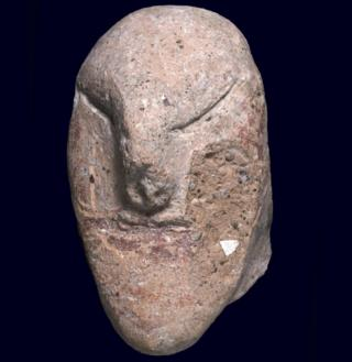 A close up image of a small stone figurine depicting a person's head