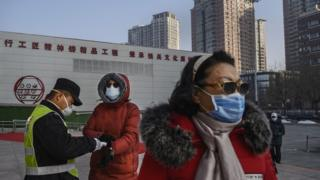A Chinese woman (left) wears a protective mask as she has her temperature checked by an official entering a park on 9 February 2020 in Beijing, China