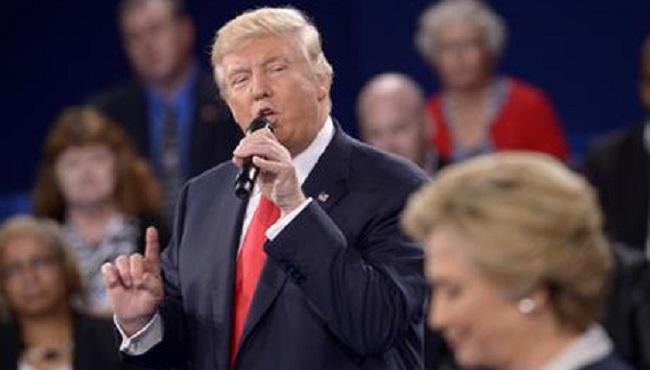 Republican presidential nominee Donald Trump speaks as Democratic presidential nominee Hillary Clinton listen during the second presidential debate at Washington University in St. Louis Sunday Oct. 9 2016