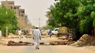 Sudanese residents walk by barricades in Khartoum on June 9, 2019.