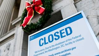 A sign is displayed at the National Archives building that is closed because of a US government shutdown in Washington, DC, on December 22, 2018