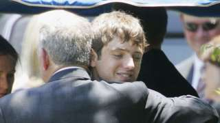 Burke Ramsey embraces his father John Ramsey at his mother's funeral